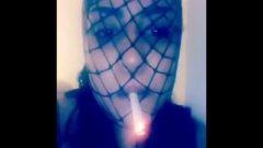 Latina Smoking In Fishnet Mask